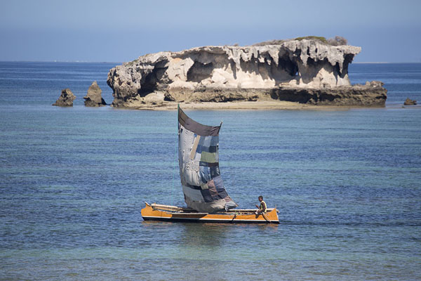 Picture of Pirogue with sail passing one of the rocky islets off the shore