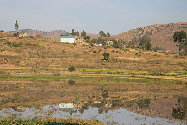 Foto van Landscape with houses reflected in lake near Anja - Madagaskar - Afrika