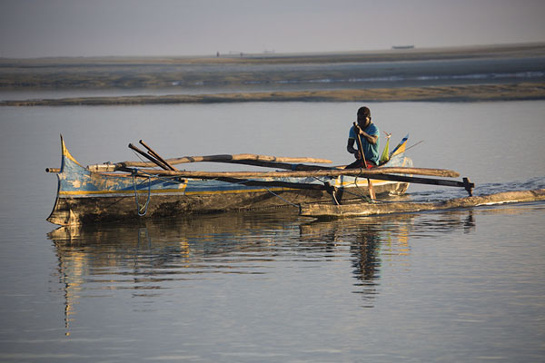 Fisherman paddling his pirogue through shallow waters | Belo sur Mer | Madagascar