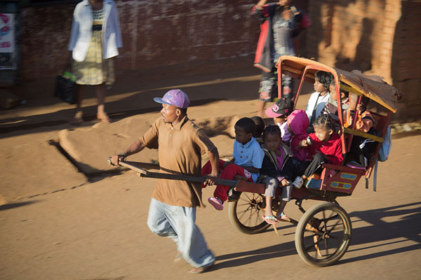 Foto van Man running a pousse-pousse with schoolkids through the streets of AmbalavaoMalagassiers - Madagaskar