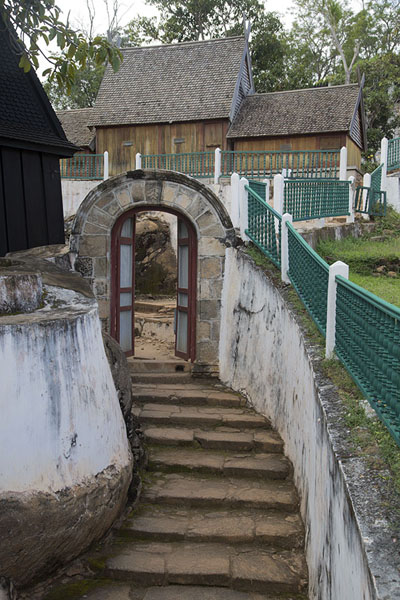 Foto van Stairs leading to the second stone gateway with the royal tombs in the backgroundAmbohimanga - Madagaskar