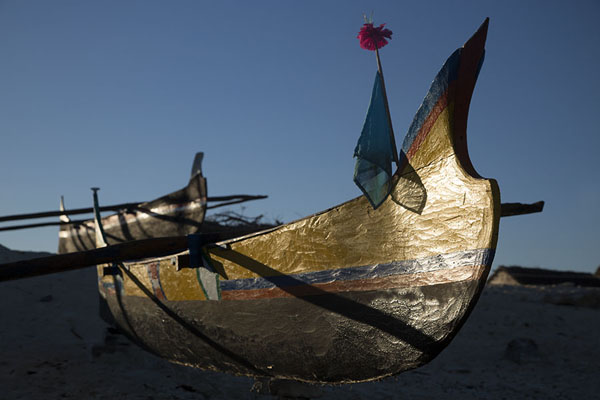 Sun casting shadows on a pirogue on the beach of Salary | Salary | Madagascar