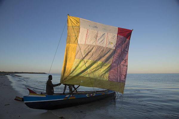 Foto de Fisherman raising his handmade sail on his pirogue for a morning catchSalary - Madagascar