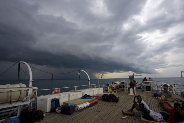 Passengers on the first class deck with dark skies over Lake Malawi | Ilala Ferry | Malawi