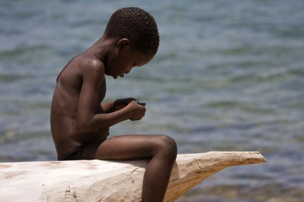 Foto van Small Malawian boy sitting on a canoe on a beach of Likoma island - Malawi - Afrika