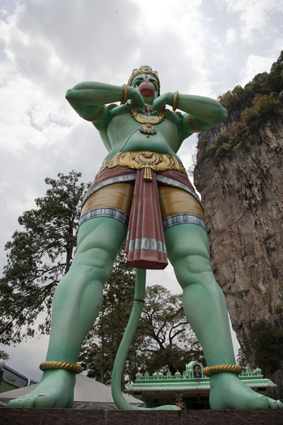 Picture of Larger than life Hanuman statue in front of a small temple at the foot of the hill in which Batu Caves can be found
