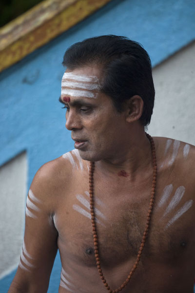 Picture of Hindu priest with body paint on the stairs of the Batu Caves