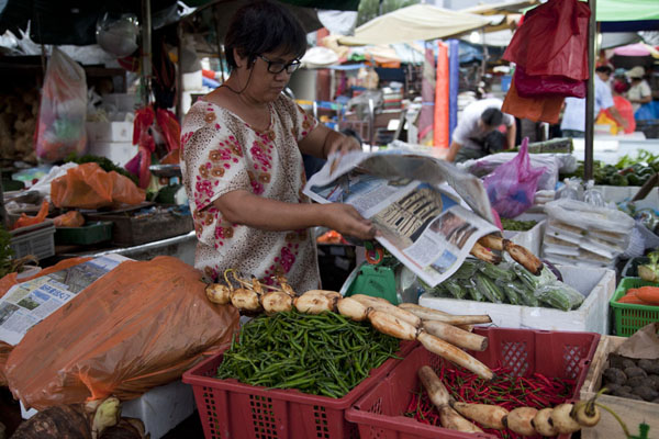 Foto de Woman selling vegetables at one of the many stalls of Pudu marketMercado de Pudu - Malasia
