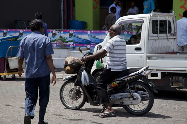 Foto van Customer on his motorbike with fish bought at the marketMalé - Malediven