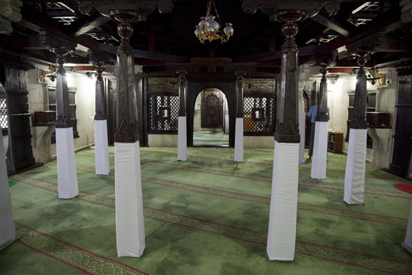 Picture of The interior of the Hukuru Miskiy, with lacquerwork and stripes on the carpet to indicate the direction towards Mecca