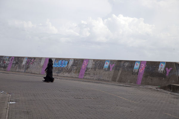 Veiled woman walking next to a seawall at the western side of Malé | Malé | Maldivas
