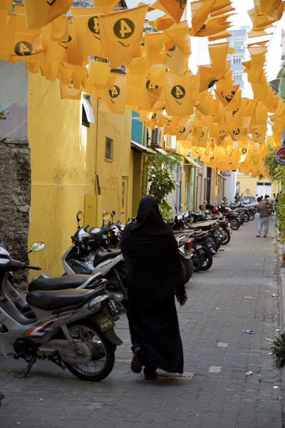 Veiled woman walking a street full of motorbikes and election flags | Malé | 马勒蒂夫