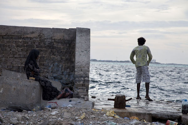 Picture of Woman waiting for her man to catch a fish at Viligili island