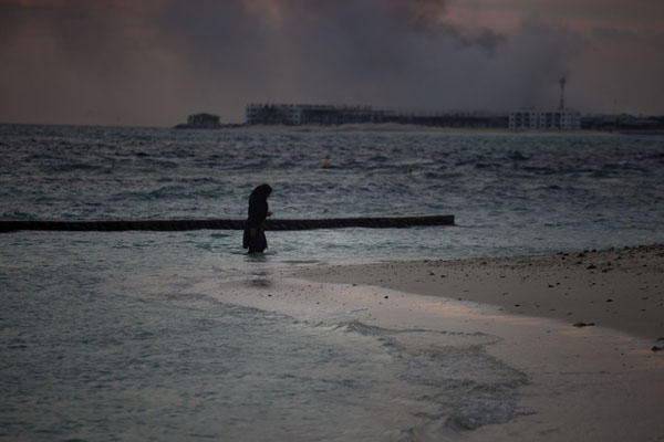 Photo de Fully dressed woman emerging from the sea at Viligili islandViligili - Maldives