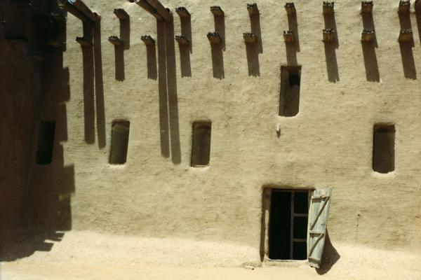 Picture of Mosque of Djenné: small door and wooden beams sticking out of the adobe wall