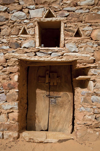 Old wooden door with decorated wall in one of the ancient libraries | Chinguetti | Mauritania