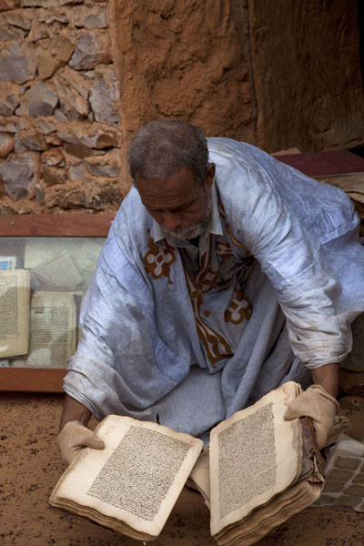 Picture of Chinguetti (Mauritania): Caretaker of one of the ancient libraries showing one of the old documents in his collection