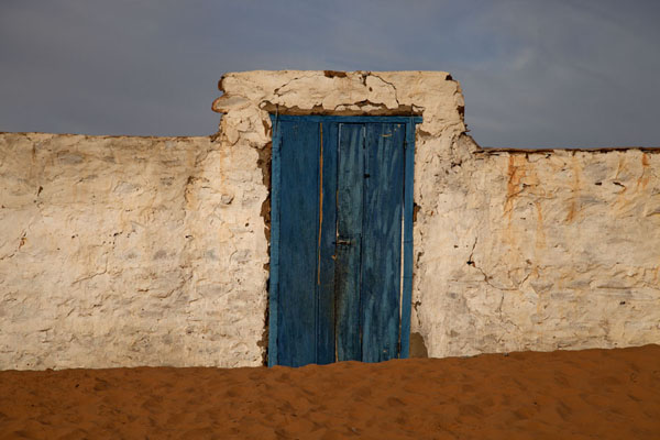 Picture of White wall with blue door and and sand in front of the building in ChinguettiChinguetti - Mauritania