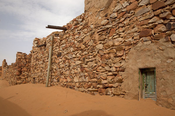 Street with sand building against the stone walls of the houses | Chinguetti | Mauritania