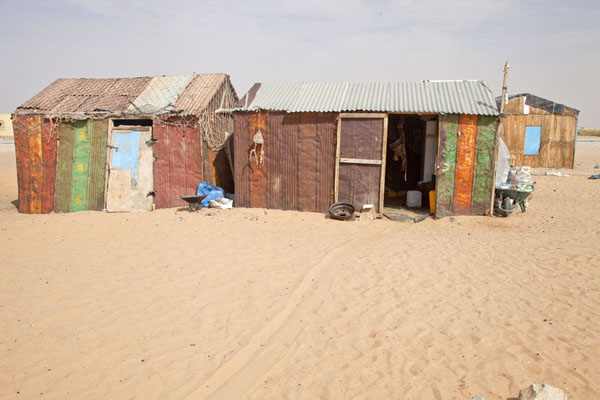 Shack with a goat hanging from the ceiling in the right hand shack | Nouadhibou Nouakchott taxi ride | Mauritania