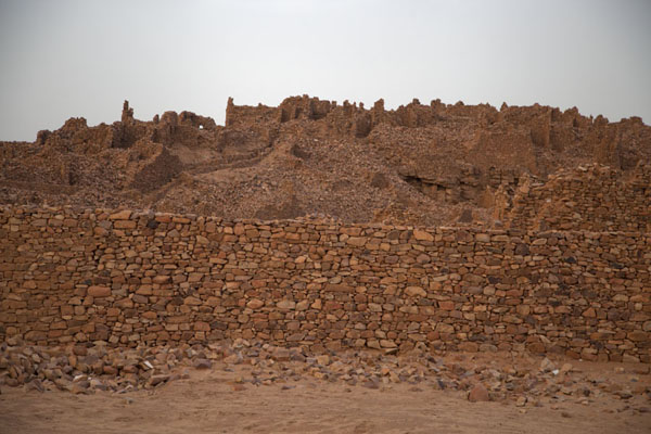 The reconstructed city wall of Ouadane with the ruins of the old city behind | Ouadane | Mauritania