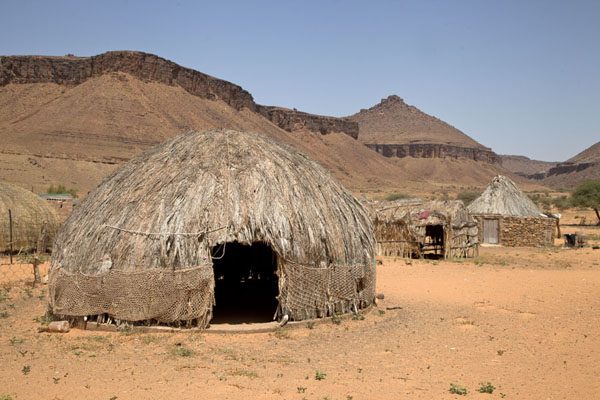 Typical huts in Terjit with rugged rocky landscape in the background | Terjit | Mauritania
