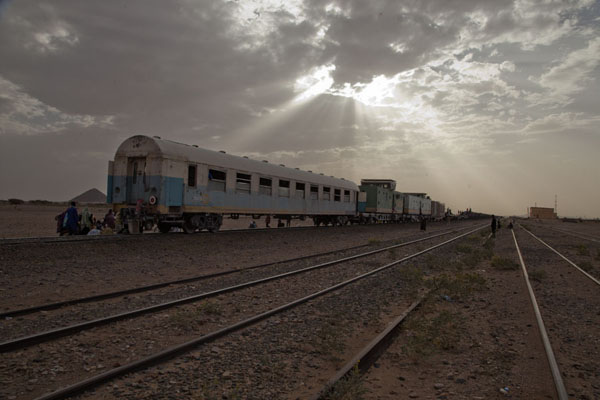 The iron ore train at a stop in Choum station just before sunset | Zouérat Nouadhibou train minerai de fer | Mauritanie