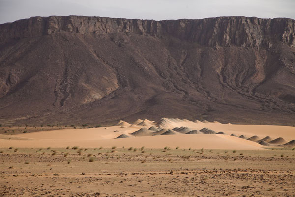 View of tabular mountains with sand dunes at its feet | Zouérat Nouadhibou ijzererts trein | Mauritanië