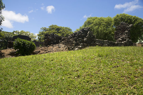 Foto de Ruined wall of the French fort rising from a green field - Mauricio - Africa