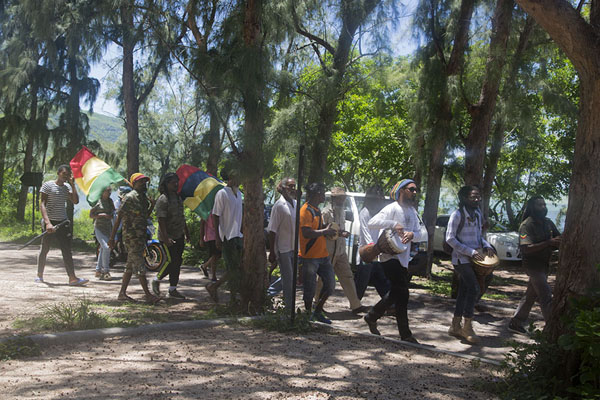 Group of people marching along the foot of Le Morne Brabant, commemorating the abolition of slavery | Le Morne Brabant | Mauritius
