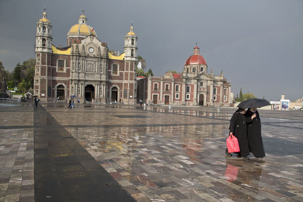 Picture of Marian Square of the Americas in the afternoon with two nuns walking away from the old Basilica and the Capuchinas Parish