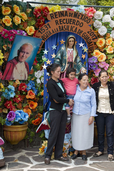 Family posing with an image of Virgin Guadalupe, fake flowers, and a picture of Pope John Paul II | Basílica de Guadalupe | Mexico