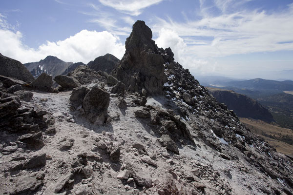 Rocky formations right on the crater rim of the Nevado de Toluca with Pico del Fraile on the far left | Nevado de Toluca | Mexico