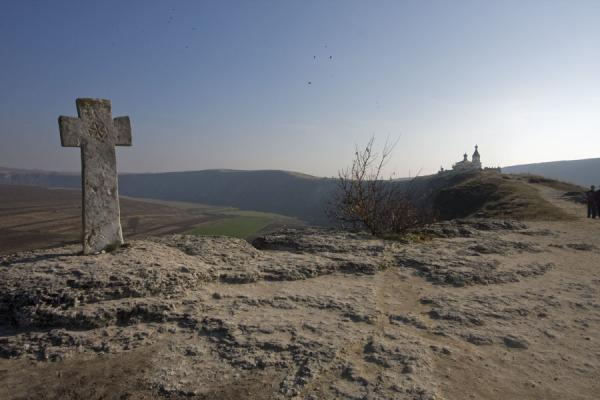 The stone cross at the edge of the cliffs, with the modern Birth of the Holy Virgin church in the background | Pestera Hermitage | Moldova