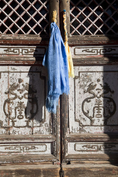 Picture of Amarbayasgalant Khiid (Mongolia): Wooden door with decorations and blue cloth in one of the buildings of Amarbayasgalant Khiid complex