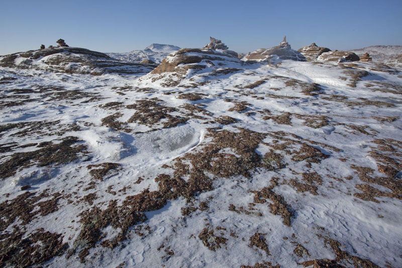 Rocky surface covered in snow with ovoos in the snow | Baga Gazryn Chuluu | Mongolia