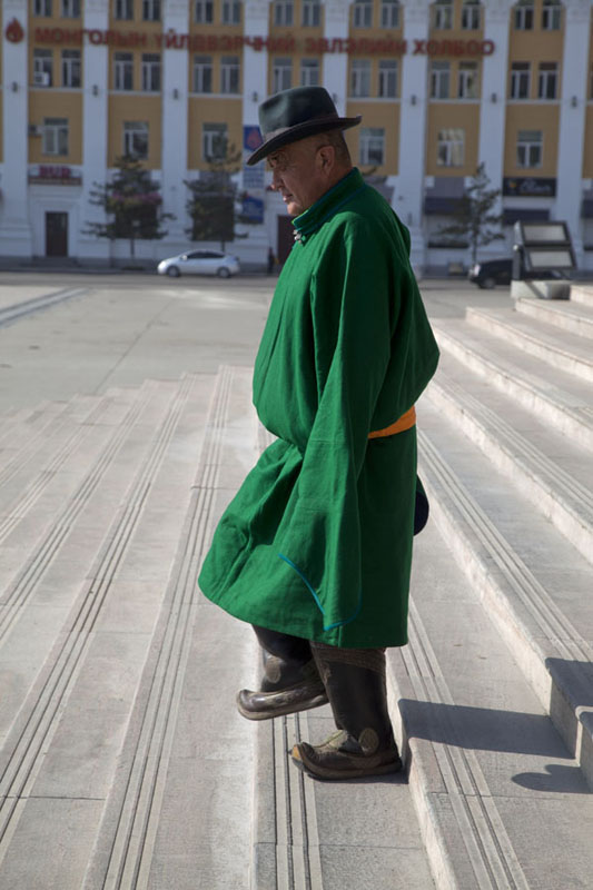 Picture of Mongolian wearing a del, traditional Mongolian dress, walking down the steps of Parliament Building