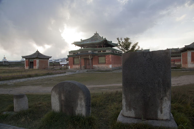 Stele with inscriptions with two buildings housing large prayer wheels, and closed temple | Erdene Zuu Khiid | Mongolia