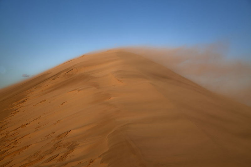 Sand blowing over the top of a sand dune | Khongoryn Els | Mongolia