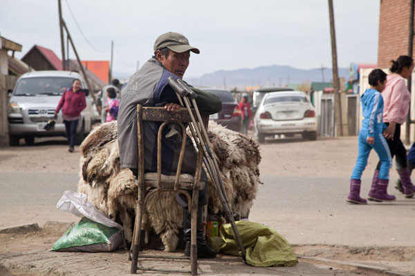 Handicapped man selling sheep skins at a street in Mörön | Mörön | Mongolia