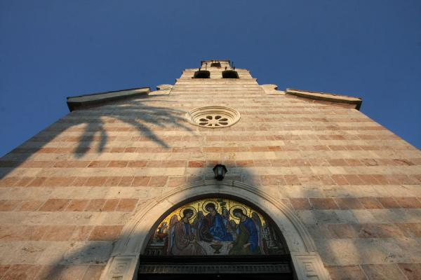 Palm tree shadow falling over the entrance of the church of the Holy Trinity |  |