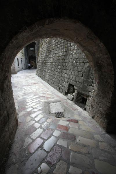 Foto van Cobble stone street under an arched passage way in KotorKotor - Montenegro