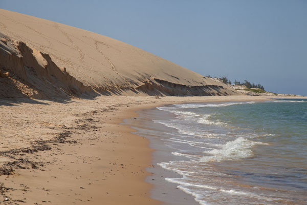 Narrow beach and sand dunes rising up steeply from the sea | Bazaruto Island sand dunes | Mozambique