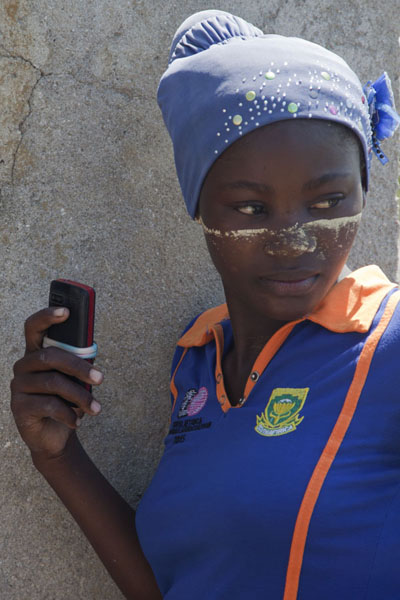 Picture of Ibo girl posing with her phone at the lighthouse of MujacaMujaca - Mozambique