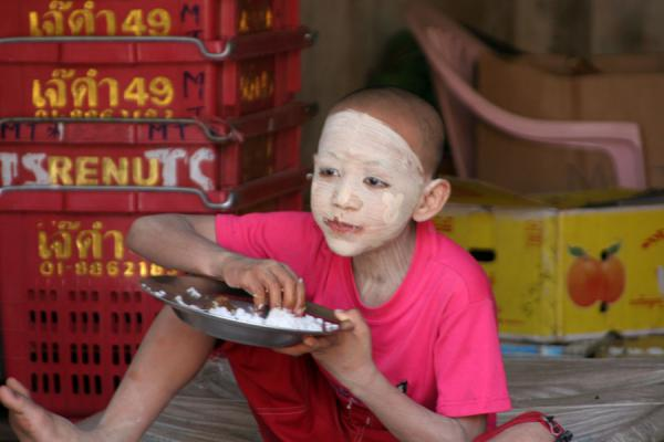 Young boy almost completely covered by tanakha having lunch | Burmese faces | Myanmar (Burma)