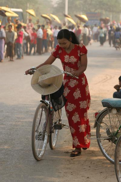 Woman walking her bike along a traditional parade in the streets | Burmese public life | Myanmar (Burma)