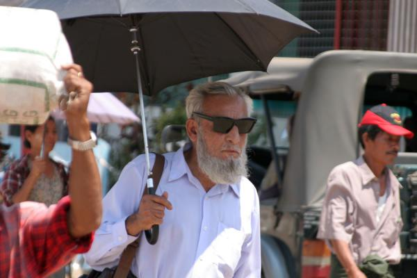 Picture of Burmese public life (Myanmar (Burma)): Burmese man with sunglasses and umbrella standing out from the crowd