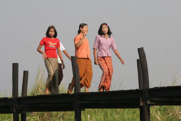 Picture of Burmese public life (Myanmar (Burma)): Laughing girls walking on a wooden bridge near Inle Lake