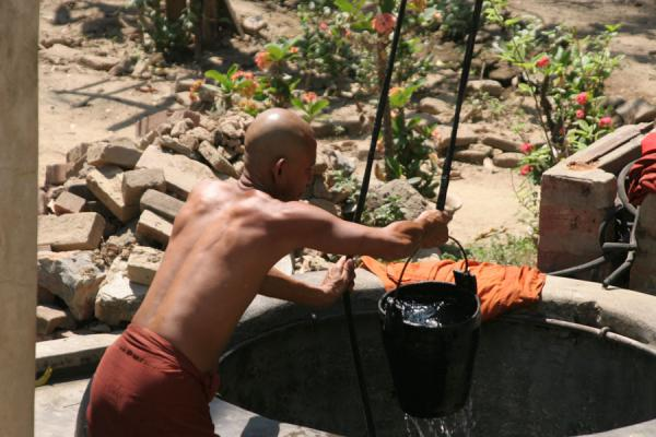 Monk washing himself with the water of a well | Myanmar monks | Myanmar (Burma)