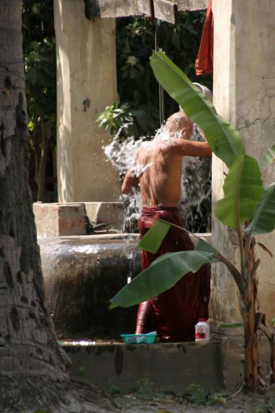 Picture of Myanmar monks (Myanmar (Burma)): Buddhist monk washing himself in the courtyard of his monastery